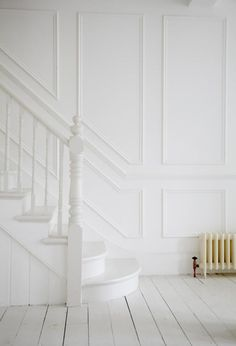 white on white, white paneled walls, white stairway, old floorboards painted white
