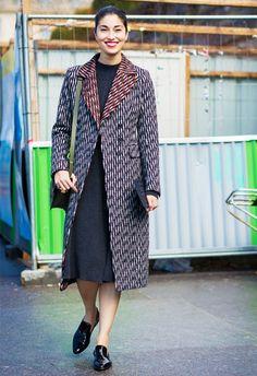 Caroline Issa wears a midi dress, printed coat, and flats
