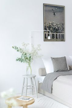"""Pared-back finishes throughout these apartments include white walls and painted herringbone floors. Colour is only present in the plants and a series of Polish tourism posters by artist Ryszard Kaja, introduced to """"combine typical hotel elements with more homely motives""""."""
