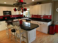 White Cabinets, black countertop and red backsplash?! Love that combo.
