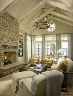 A beautiful living room decorated with neutral colors and breezy window treatments. Click to see some of the most popular window treatment trends and get ideas for your home!