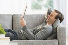 USA, New Jersey, Jersey City, Man lying on sofa watching tablet pc - Tetra Images/Brand X Pictures/Getty Images