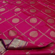 Nothing crowns rani pink better than gold! Gold checks smother this spinel pink #silk sari, encasing coin-sized gold floral buttis in alternate squares. The morning evening border in gold is much loved these days wherein the smaller top border has a hint of coral and purple and is woven with elephant, rudraksh and peacock motifs. The border at the bottom is broader and proudly displays the same motifs along with a band of #bavanji border. An offering from Sarangi's pretty pinks. Code…