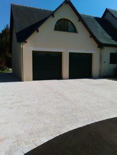 Cour en enrobé noir avec un accès garage en pavage.