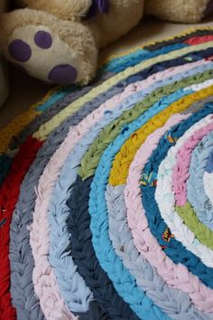 "Colourful Rag Rug Tutorial (this doesn't look crocheted, but it is ... it's made with tarn, and consists simply of a crochet chain stitched with thread so that the braided looking side is ""up"", then a sc border is added to finish it off.)"