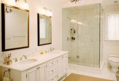 double vanity. frameless shower. white tile with white marble.