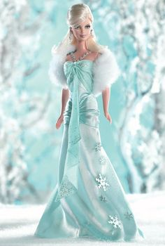 The magic of winter inspires this cool, blonde beauty wearing a long, ice blue charmeuse gown. It has a silvery, glitter printed ice blue chiffon halter with exquisite silvery seed bead detail. She also comes with a snowy, faux-fur stole and silvery earrings — the perfect accessories to complement winter's elaborate display!
