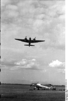 Ju 88 aircraft in flight in Germany, 1943; note Bf 110 fighter on ground