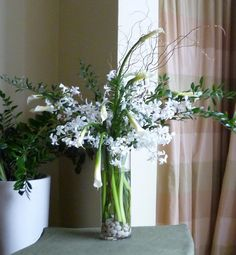 This is a floral arrangement that features dendrobium orchids and calla lilies in a white color scheme with accents of curly willow branches.