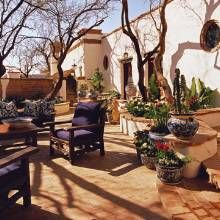 Talavera pots punctuate the enlarged entry courtyard . The round windows are a typical Mexican design element.