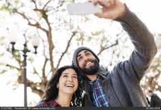 Young happy couple taking a selfie outdoors - stock photo