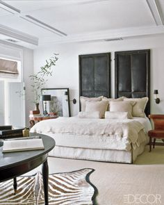 Antique bordello doors serve as a headboard in this master bedroom designed by Darryl Carter.