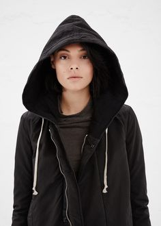 Long-sleeved, hooded and insulated coat in a washed black cotton and nylon blend. Snap closure placket with hidden zipper closure. Flap and vertical welt pockets in front. Interior zip pockets. Drawstring closure at collar, waist and hem. Hood and interior lined with quilted cotton. Hem detail with split on both sides, with rear split connected by drawstring. Machine wash warm, lay flat to dry.