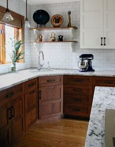 Beautiful rustic, saddle brown stained cabinets, white subway backsplash, and antique white upper cabinet combo.