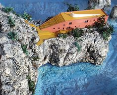 Casa Malaparte, Capri, Italy. Designed in 1937, it sits on a cliff almost 40 meters above sea level. It can be accessed either on foot from Capri or by boat, in which case you have to climb the stair cut into the cliff. Rosso veneziano color.