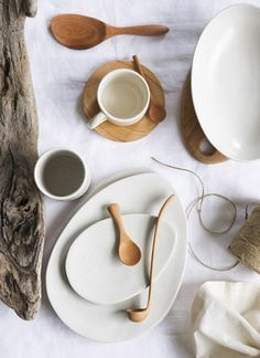 """Australian brand """"attia"""" stoneware & wood pieces are represented in a clean, minimalistic tabletop style. These neutral pieces are placed evenly apart causing your eye to flow from one piece to the next."""
