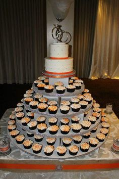 Vibrant orange accents this cupcake tree with hydrangea decorated cupcakes topped with a 2-tier cake. #wedding #weddingcakes #cupcakes