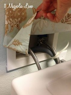 laundry room hookups curtain, made with a small scrap of fabric to cover the faucets and hoses behind the washing machine.  Apply with hot glue if the plastic border doesn't pull out from the wall