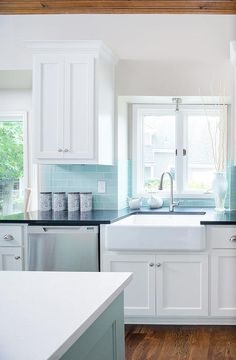 Tiffany blue kitchen features white cabinets adorned with nickel cup pulls paired with black quartz countertops and a tiffany blue subway tiled backsplash.