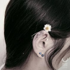 Fine line flower tattoo on the ear.