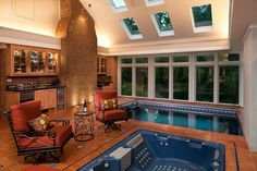 This sunroom works overtime as a kitchen, lounge, and spa. Exposed brick, terracotta tile, and rust-toned upholstery add to the natural vibe. This is an in-ground Endless Pool and hot tub. Indoor Pools, Piscina Interior, Pool Picture, Pool Photo, My Pool, Pool Spa, Wave Pool, Elderly Home, Dream Pools