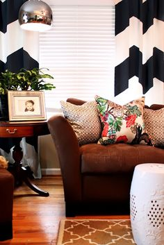 Colorful throw billows on caramel leather couch and patterned curtains for living room.