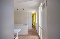 #tissellistudio kitchen with white cabinets, wooden floor and a yellow coloured mirror