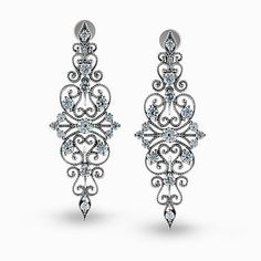 Presenting an intricate vintage style design, these white gold dangle earrings are accented by .67 ctw round white cut diamonds. #diamondjewelry