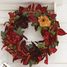 How to make it: Use a floral pin to attach one end of a 6-foot silk leaf and berry garland to the back of a 16-inch grapevine wreath. Then, tightly wrap the garland until the wreath is covered. Cut off any excess and pin the loose end to the back. To add even more bursts of color, pop the heads off several silk blooms and hot-glue them to your wreath... from Quick and Simple.