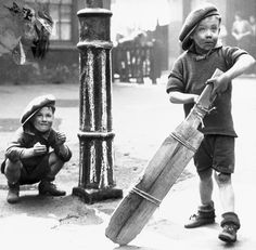 I think he needs a bigger bat! Kids playing Cricket in the street in 1934.