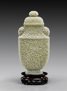 """Fully reticulated, Chinese celadon-white jade covered vase; of flattened form set on a shallow flared foot, the finely pierced-carved entirety depicting meandering foliage with plum and lotus blossoms, with two domed handles and similarly domed finial; H: 10 7/8"""", openwork wood stand"""