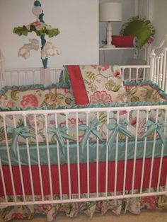 A musical mobile and round pillows coordinate with the aqua and melon floral crib bedding