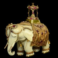 Unusual carved ivory ornamental elephant its head mounted with a gold head-piece decorated with rubies and pearls with gold wire detailing suspending small gold bells, its back covered with an ornate gold cloth with a studded pattern set with further rubies and pearls beneath a yellow gold howdah Indian circa 1890.