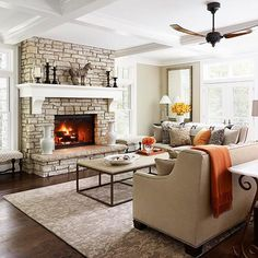 a neutral living room with a stone fireplace, white mantel & coffered ceiling