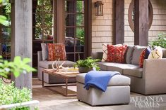 "Woodbery covered a sectional from the couple's former residence in a Perennials fabric to make it suitable for outdoor living. ""I went to a rug dealer and we had old rugs in need of repair made into pillows,"" she says. ""They play off the rug and window treatment in the billiards room."""