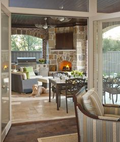 Glass doors lead out from the living room to the covered patio. The patio has a light beige tile floor, dual ceiling fans to circulate air on a hot summer's day, and a large, dominating fireplace in stone. A television is hidden behind closed doors above the fireplace. A stone cooking area with a grill connects directly to the fireplace.