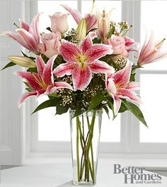 Pale pink roses collaborate with the magic of Stargazer Lilies, displaying thier fragrant fuchsia petals amidst waxflower accents