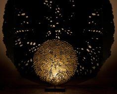 DDUMA Piccola scultura di forma rotonda, riproduce in bronzo un pizzo degli anni 20 italiano di grande raffinatezza. L'opera è fissata alla base in ferro arrugginito trattato a cera nera, sulla quale è inserito un piccolo led che puntando la sua luce sulla scultura ne proietta l'ombra ingrandita.  Dimensioni: Ø32,5 cm