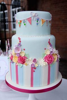 Gorgeous pastel floral cake with colorful party flags decoration