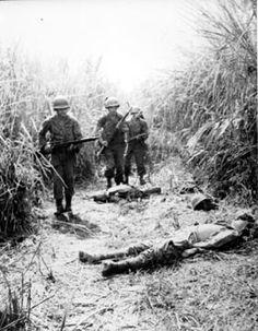 MERRILL'S MARAUDERS - North Burma ____ February - March, 1944. Marauder column passes bodies of Japanese killed shortly before in attempted ambush of a preceding I & R Platoon patrol that was advancing along a Burma trail through high elephant grass.