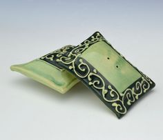 """Recently I have been fascinated by pillow shapes and I saw it as another surface to do my decoration which inspired by the colors and embroidered fabrics of India.  This is glazed in soft green and green swirl pattern with slip decoration done freehand to match the set.  Approx Dimensions: 3.5"""" length x 3.5"""" wide x 1.5"""" height  All my work is made from Stoneware. After the pieces are made, they get fired once in a bisque fire and then high fired with durable glazes that will not fade. All…"""