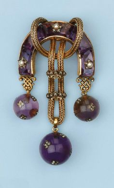 A horse-shoe shaped body set with amethysts, pearl and diamond set stars, the centre with rope tied gold thread strung with two diamond set crown slides, supporting 3 amethyst spheres encrusted with rose-cut diamond set four-leaf clover appliques, circa 1870