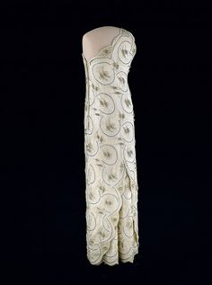 Nancy Reagan's Inaugural Gown, 1981 (back) Nancy Reagan wore this white beaded one-shouldered sheath gown of lace over silk satin to the 1981 inaugural balls. It was designed by James Galanos - National Museum of American History Vintage Gowns, Vintage Outfits, Vintage Fashion, Vintage Clothing, Nancy Reagan, Ronald Reagan, First Lady Of America, White Gowns, Historical Clothing