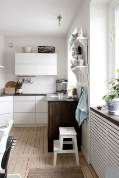 Kitchen inspiration: the natural floorboards and dark worktops give this simple handless white kitchen character. Clever radiator cover with dark shelf on top tie in with the colour scheme and provide a nice display area in the window recess. Hemma hos Nanna from Lovely Life.