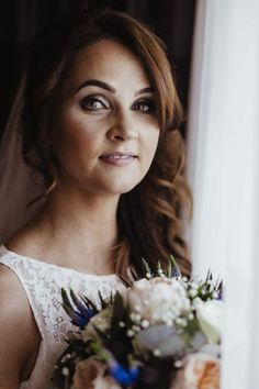 Bride in white holding flowers. Photograph by Dublin-based professional photographer Olga Hogan.