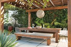 The new outdoor dining terrace features a custom Douglas fir table and benches from Mortise & Tenon, and a rattan globe pendant from Inner Gardens lights the alfresco space. Two vintage Bertoia chairs, found at Amsterdam Modern and powder-coated, offer additional seating.