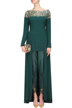 This set features a forest green high low cape in crepe base appliqued with matching green cutdana beads and crystal leaf pattern embroidery on the front and back neckline. It has nude sheer net detailing on the yoke.