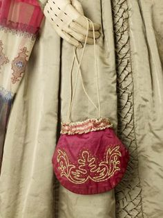 Reticule   Museum of London; crimson silk decorated with cream silk ribbons and an embroidered motif, closes with a cord drawstring, c. 1831-1850