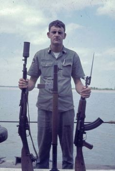 A sailor displays three weapons: (L-R) Mosin Nagant (or variation of) with what is potentially a grenade launcher attached, an RPG, an AK-47.