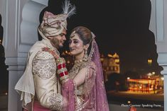 Bride pink and white shimmery Rimple and Harpreet Narula lehenga and groom in off-white and gold sherwani by Sulakshana Monga for the wedding at Jaipur